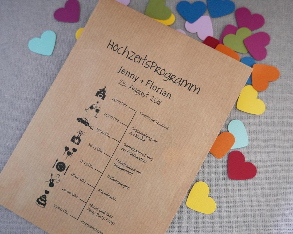 Hochzeitsprogramm auf Kraftpapiertüte gedruckt mit farbigen Konfettiherzen